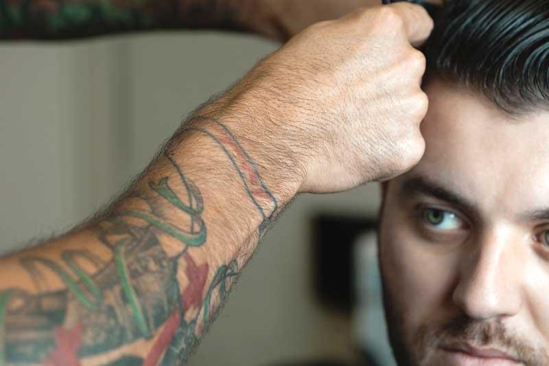 A barber in Prescott, AZ performing a men's haircut.